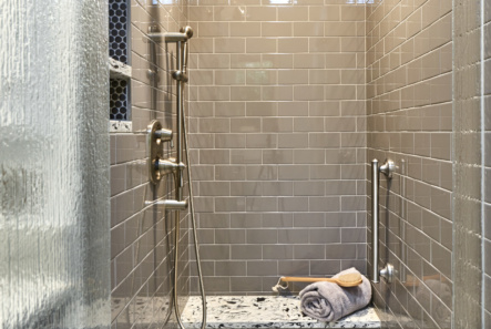 gray tile shower with quartz bench for seating