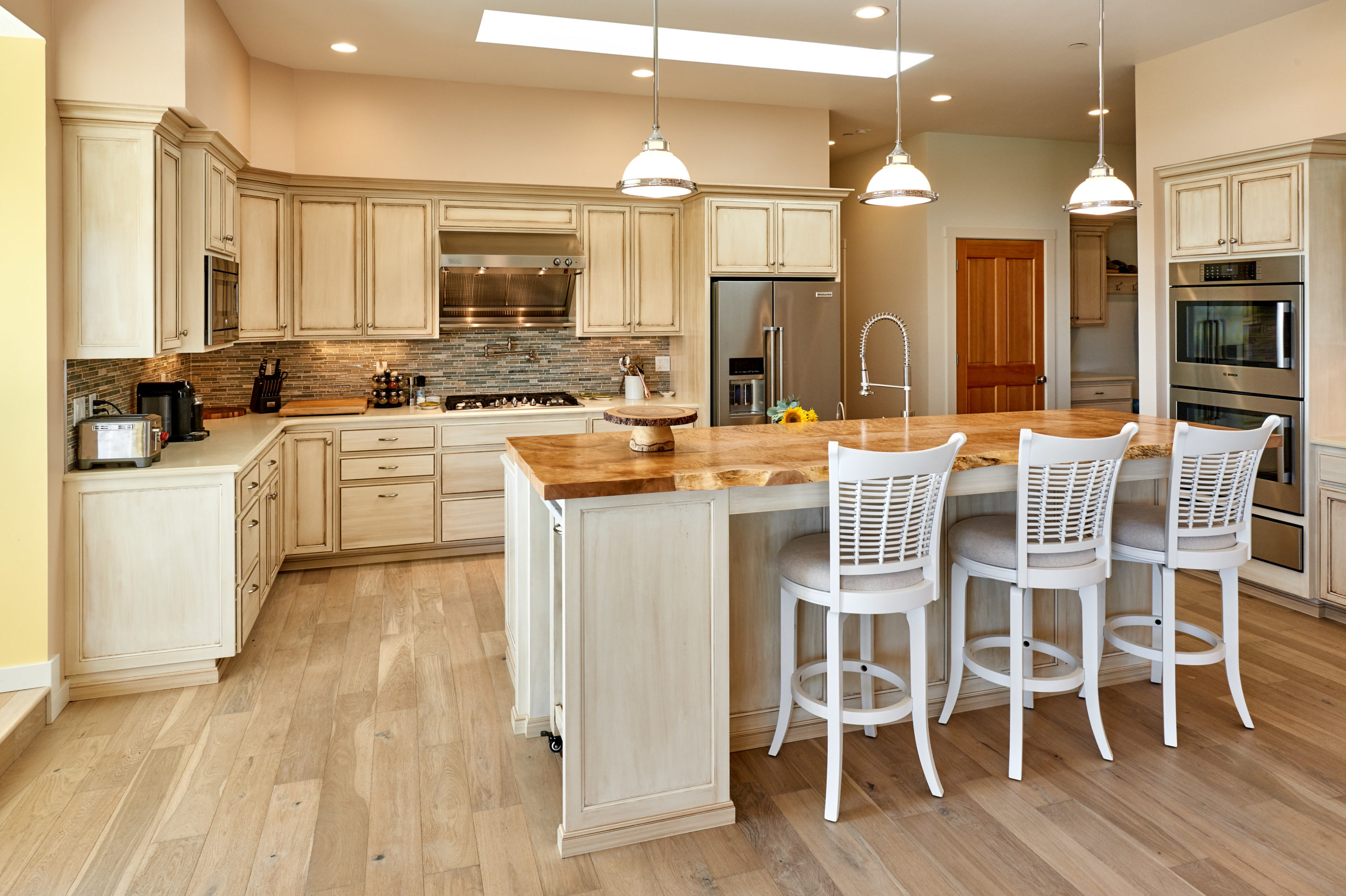 Pendant lights above kitchen island with a perimeter of white glazed cabinets