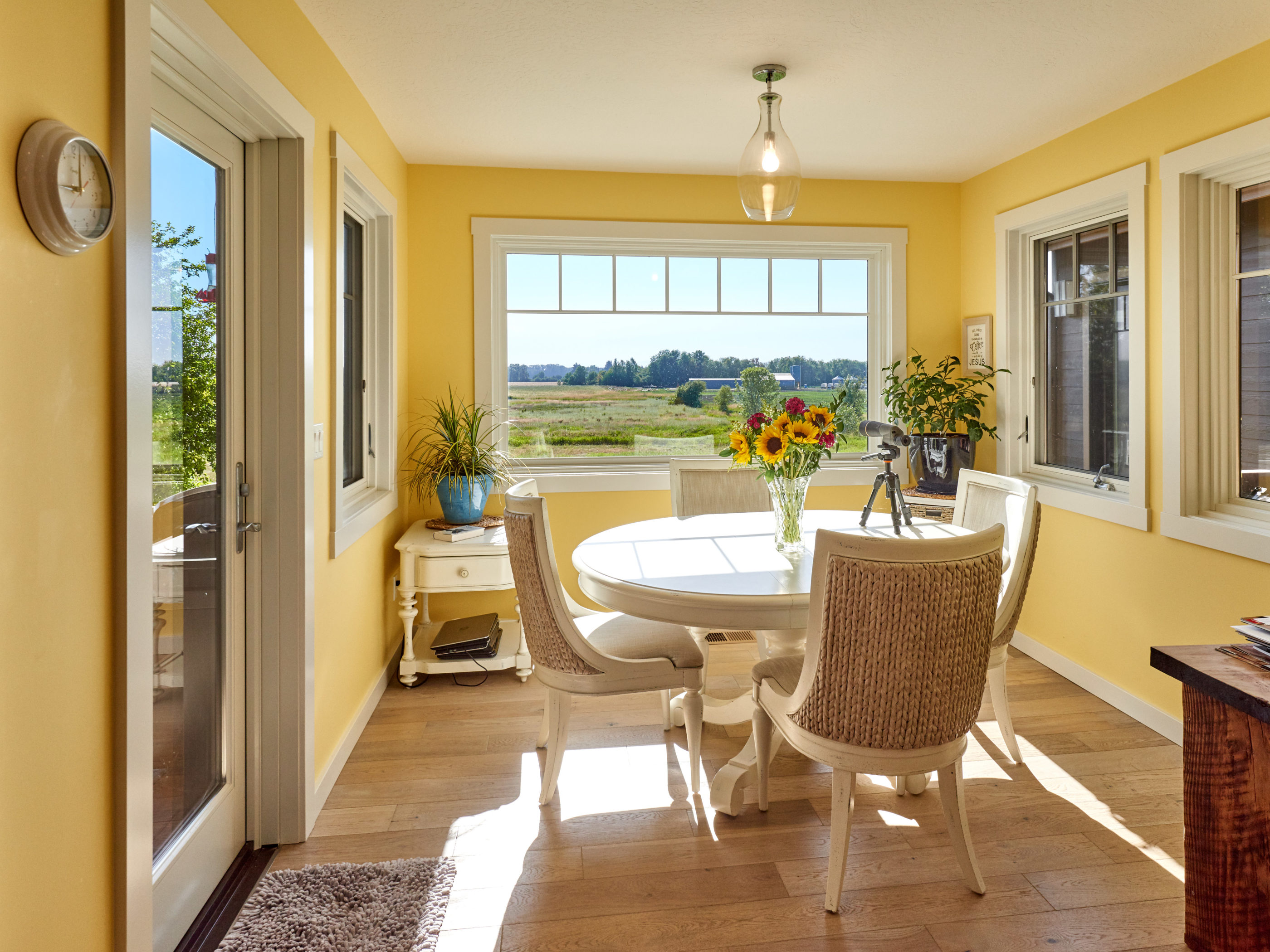 dining area with bright yellow walls and white dining furniture