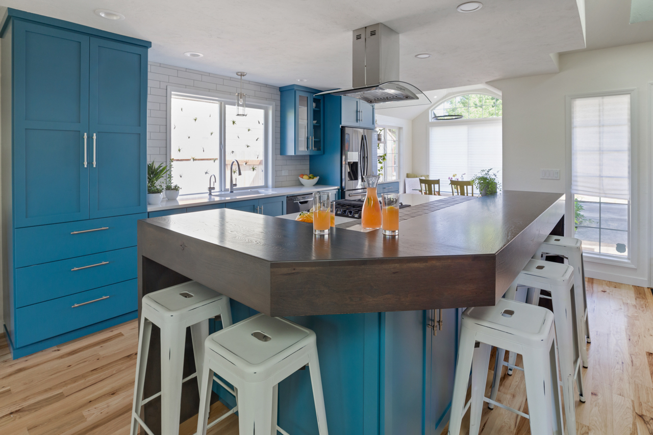 Blue cabinets under kitchen island with white bar stools
