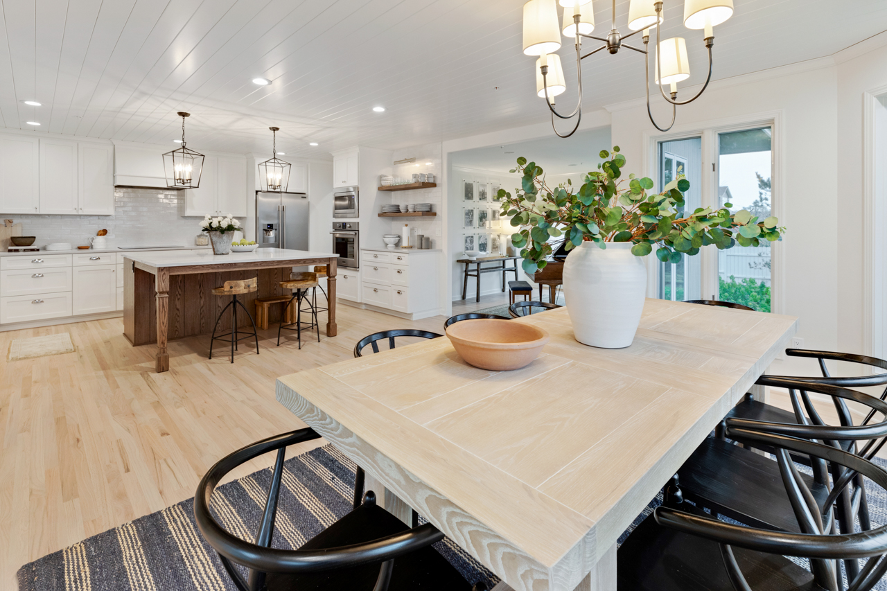 Dining room table in open kitchen with hardwood floors
