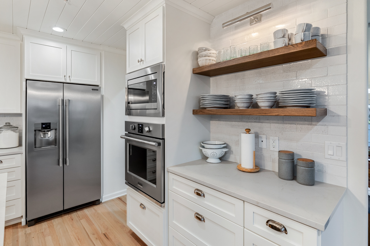 Open shelves above white cabinets and countertops
