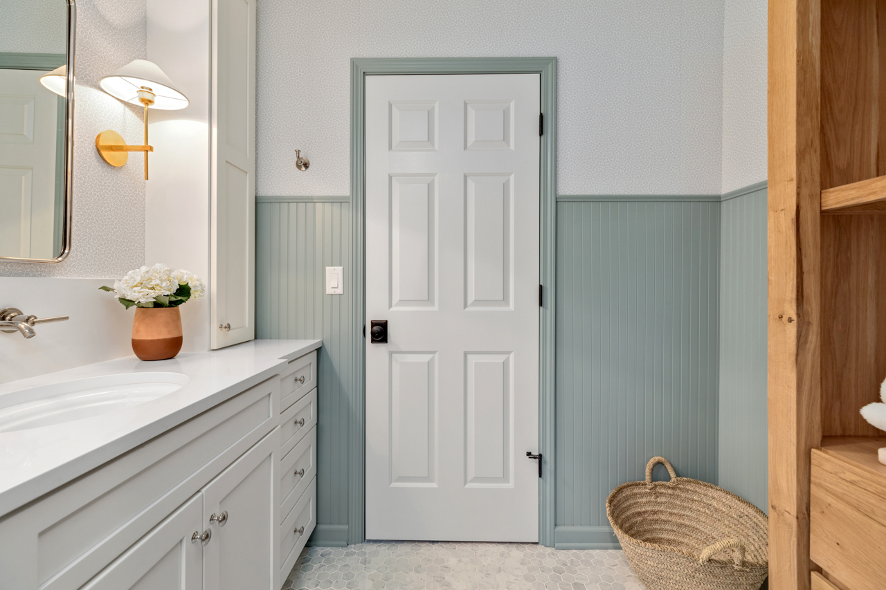 White interior door with blue trim and wainscotting in small master bath