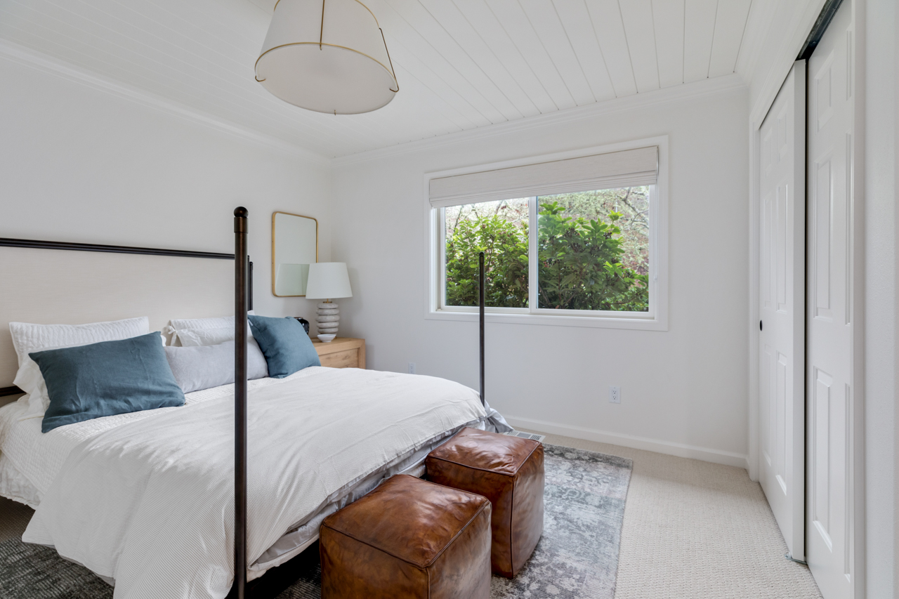 White bedroom with decorative accents on bed and nightstands