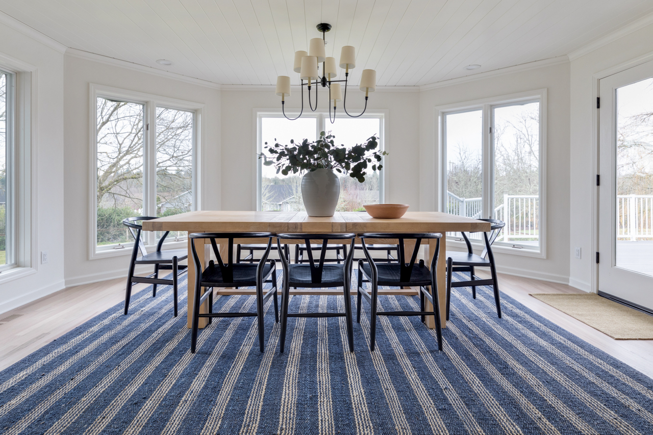 Light wood dining room table with black chairs on a blue area rug