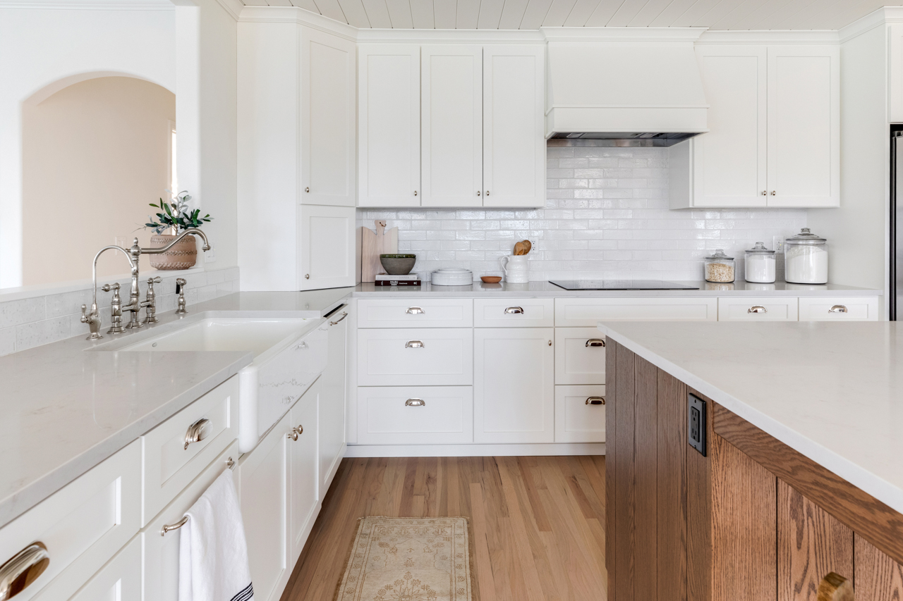 White cabinets above and below white farmhouse sink
