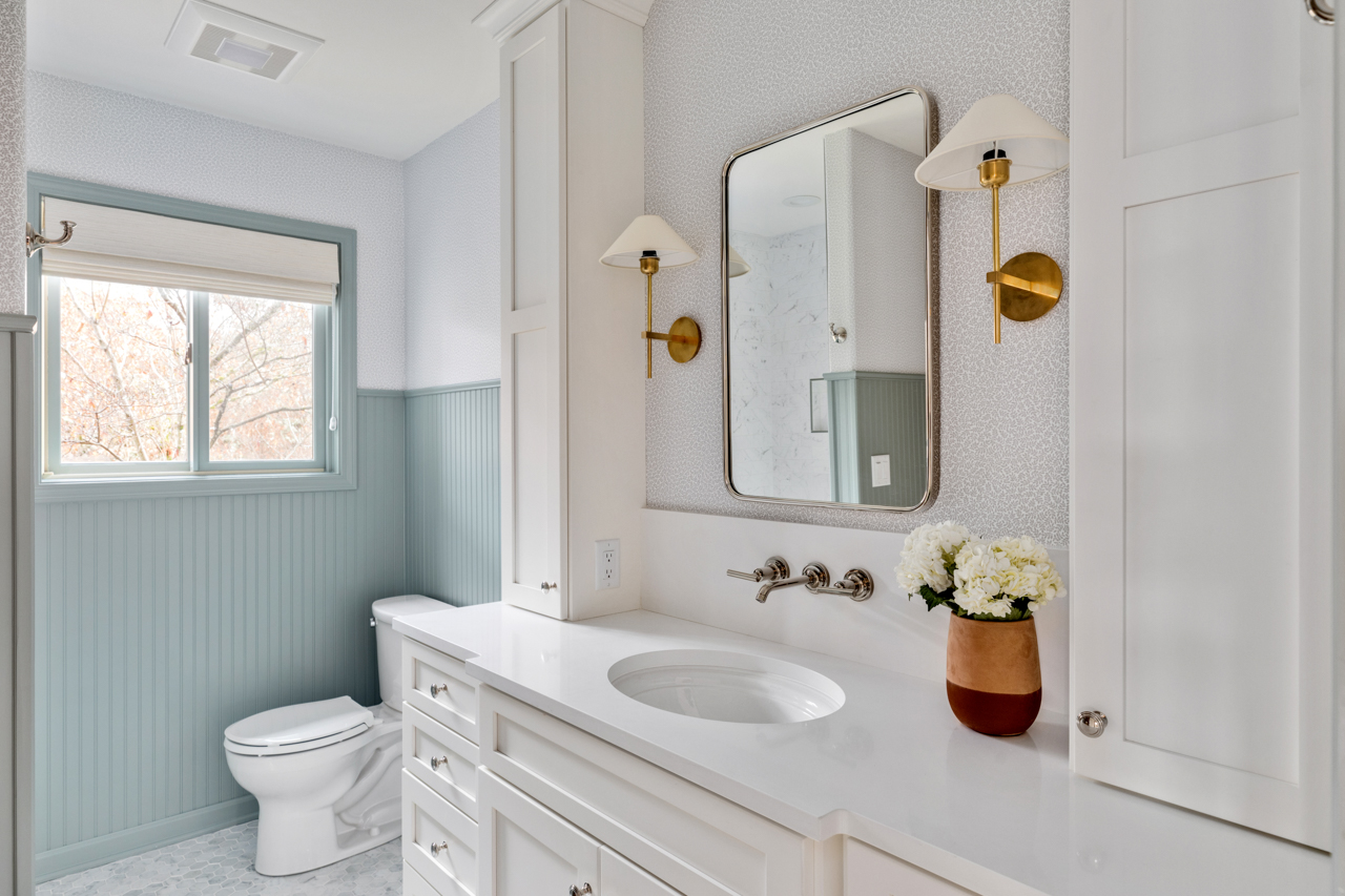 Bathroom with blue wainscoting, white cabinets and countertops, and wall mounted lights