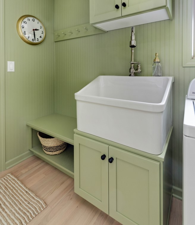 Large farmhouse sink in green laundry room