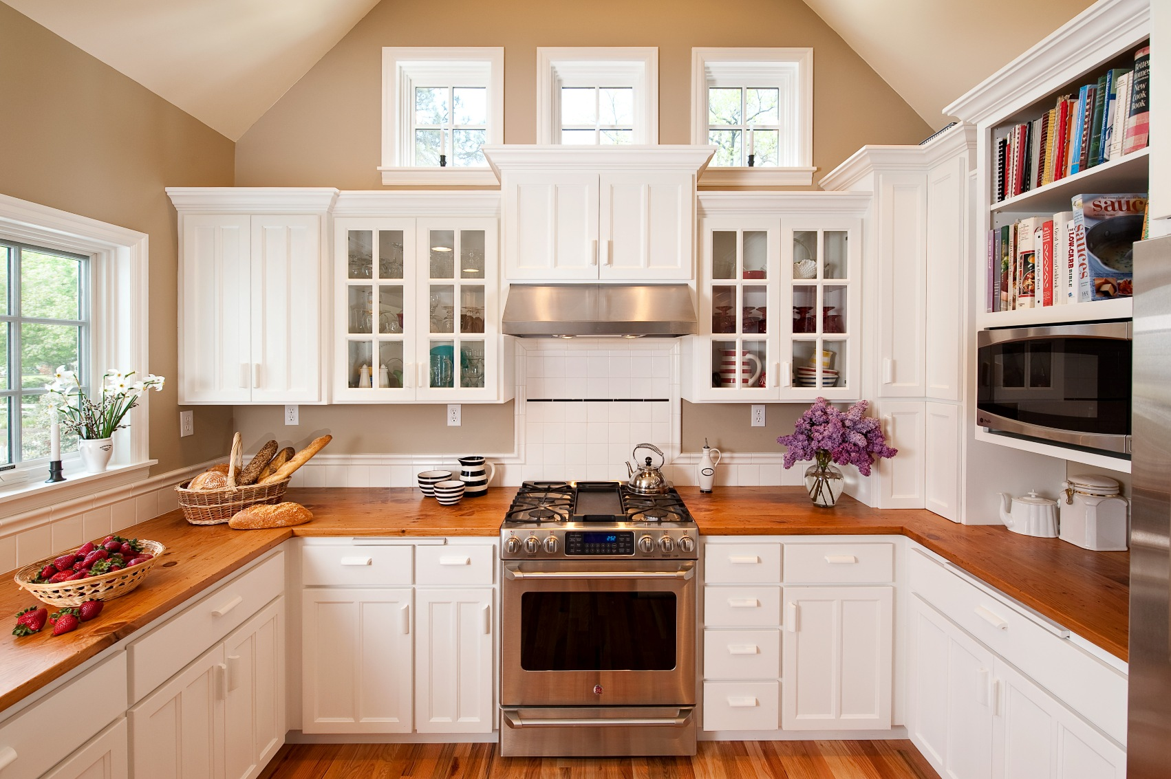 The look of the kitchen cabinets was kept simple in this classic white kitchen using panel doors with a center mullion, glass doors, and a white tile backsplash.