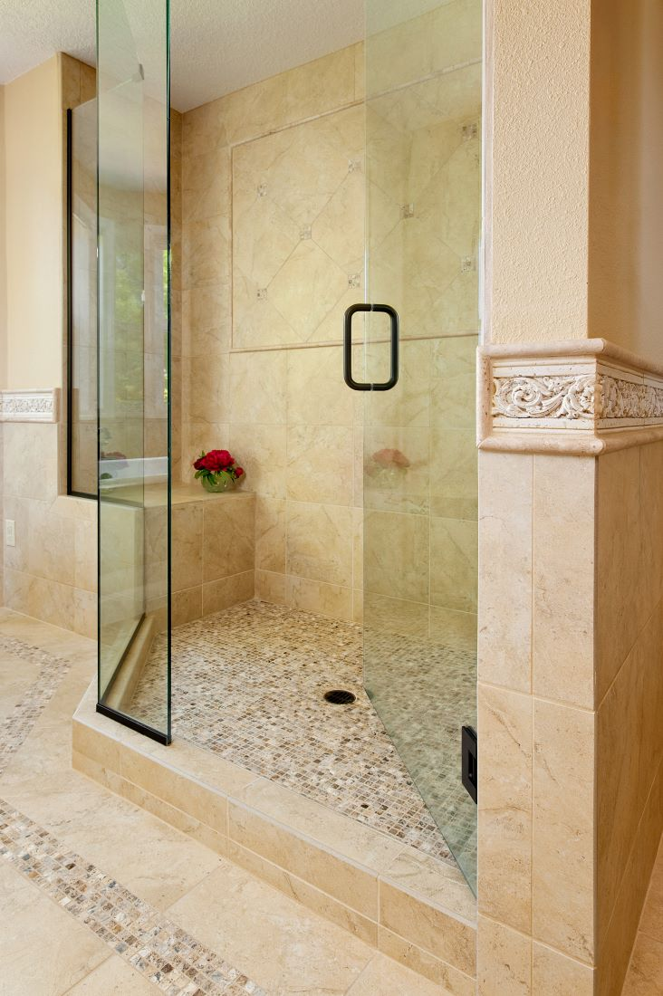 The fully tiled shower includes a frameless glass door, bench, shampoo niche, and rain showerhead.
