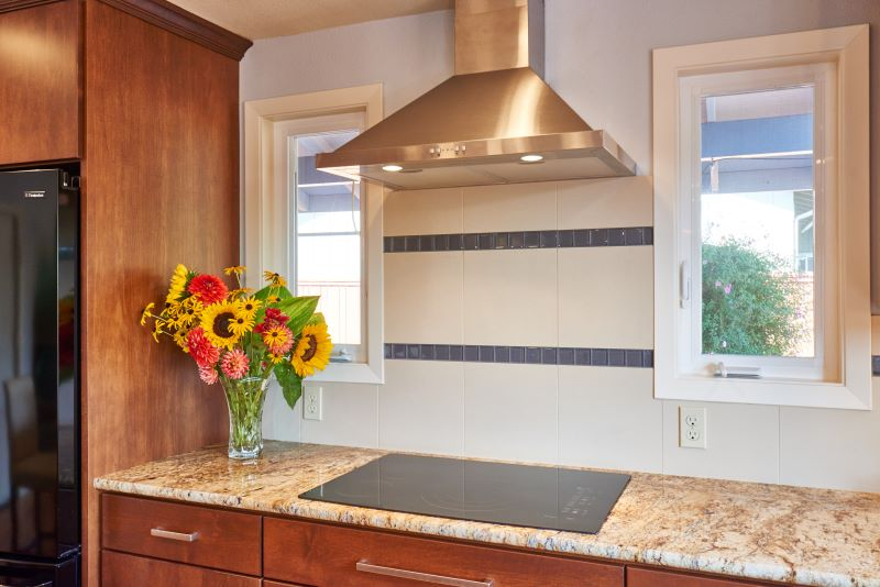 The stainless steel Broan hood in the remodeled kitchen complements the pendent fixtures.