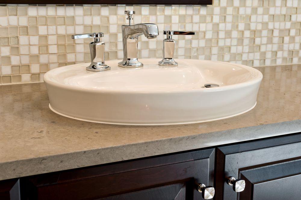 Glass mosaic backsplash tiles harmonize with the quartz counter in this bathroom remodel.