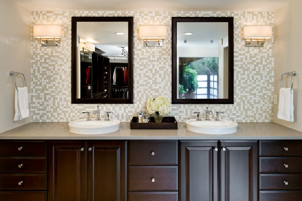 White Kohler semi-vessel sinks on the dark wood vanity create an exquisite contemporary look.