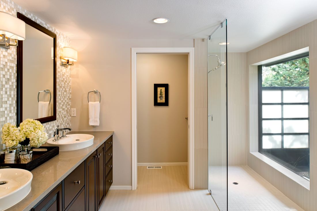 A floor-to-ceiling glass wall allows natural light to fill the remodeled master bathroom.