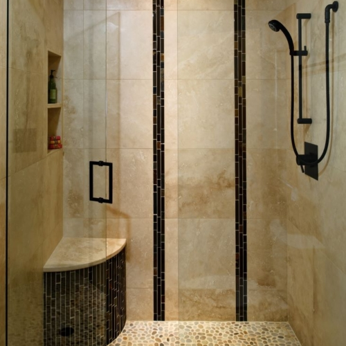 """The remodeled bathroom features a stunning shower with accent tiles installed vertically to evoke the look of bamboo. The floor tile is United Tile Island Pebbles """"Maluku Tan"""""""