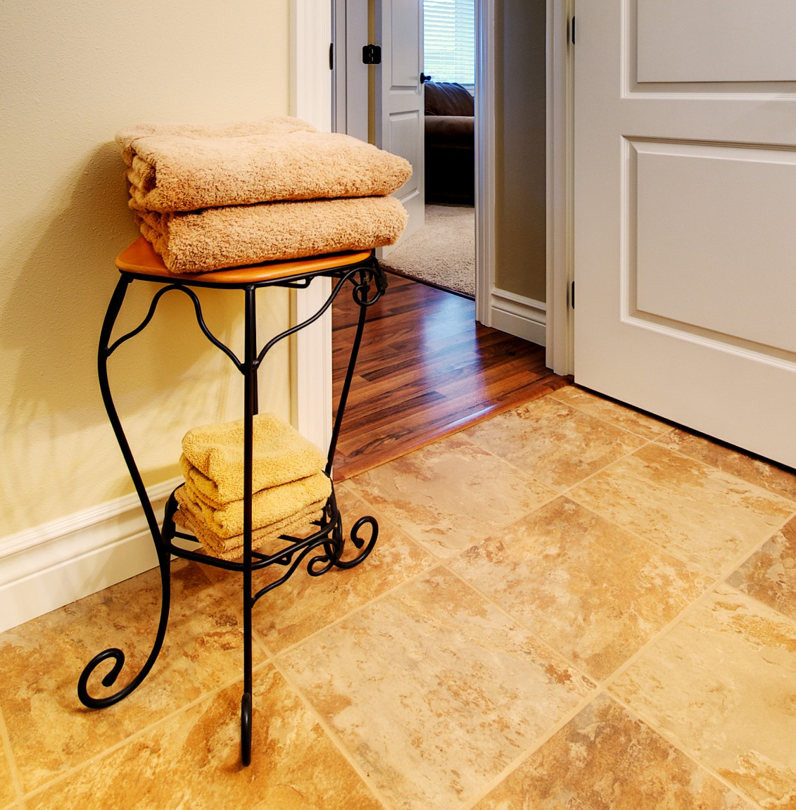 Tile is shown on the bathroom floor and Wilsonart maple laminate flooring for the hallway.