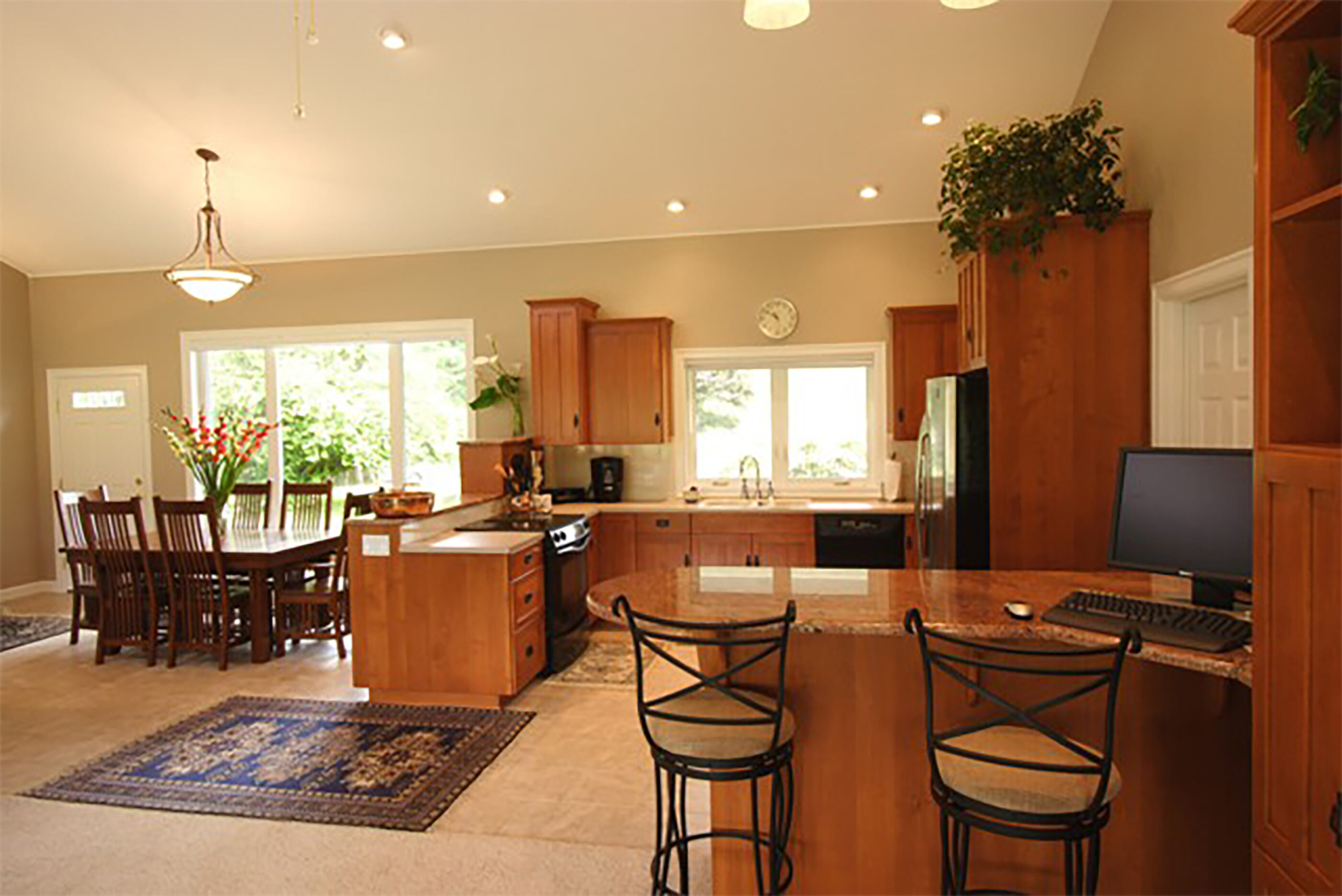A granite bar divides the living and kitchen areas can work as a computer center or bar for entertaining.
