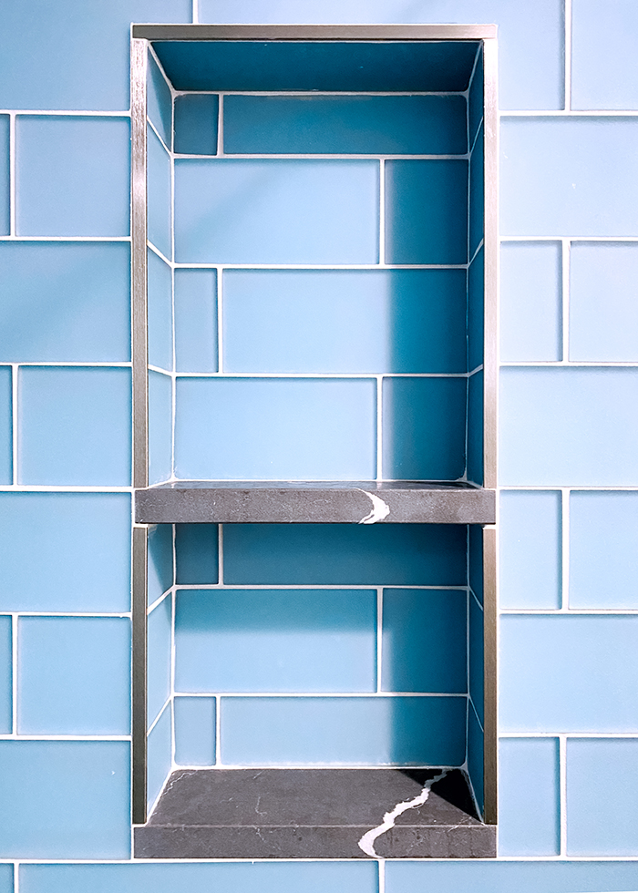 Tiled niche with blue frosted glass tile and dark grey quartz ledge