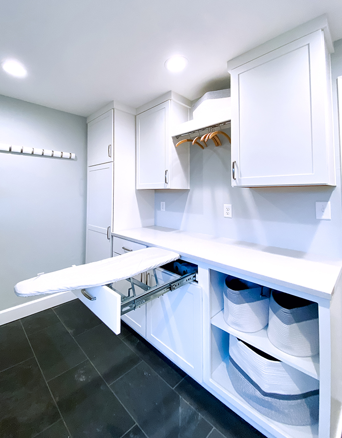 Laundry room storage cabinets with open basket storage and iron board pull-out